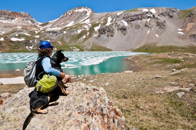 Hiker and Dog Sitting on a Rock at Ice Lake