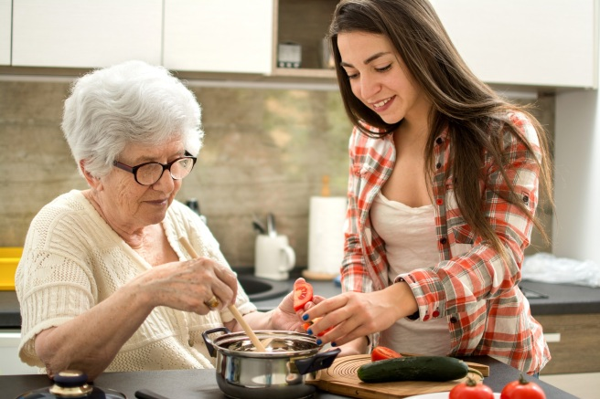 Grandmother and granddaughter cooking in the kitchen.