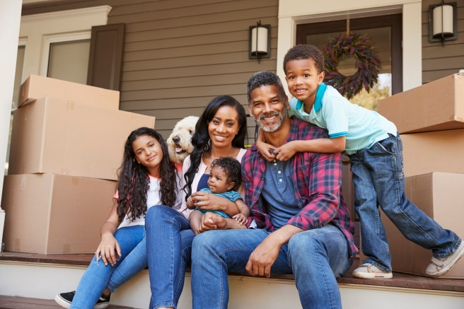 Family With Children And Pet Dog Outside House On Moving Day